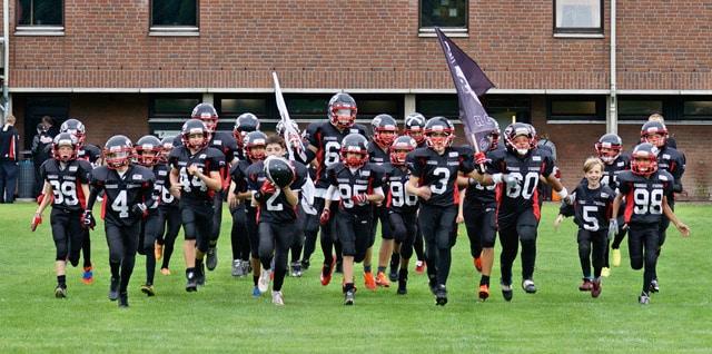 Die U13 der Panther stürmt aufs Feld, wo die Langenfeld Longhorns schon auf sie warten. - Foto:: Manfred Kühne